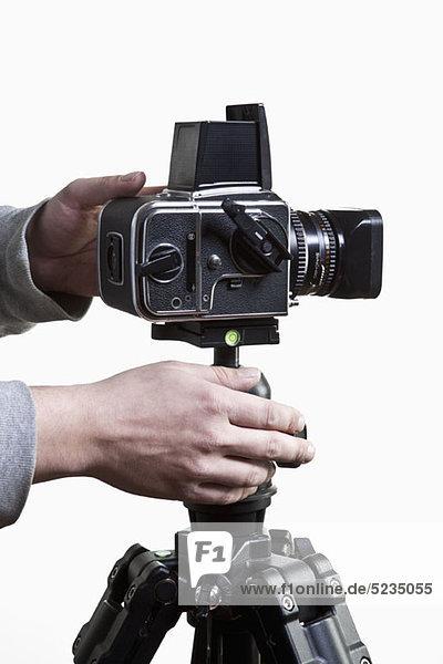 Ein Fotograf beim Einstellen einer Mittelformatkamera auf einem Stativ  Nahaufnahme der Hände