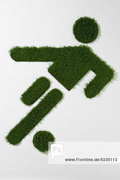 Eine Grasfigur beim Fußballspielen