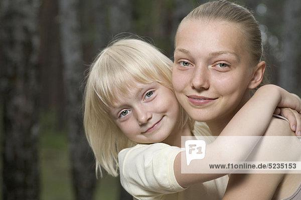 Zwei Schwestern  die sich im Freien umarmen.