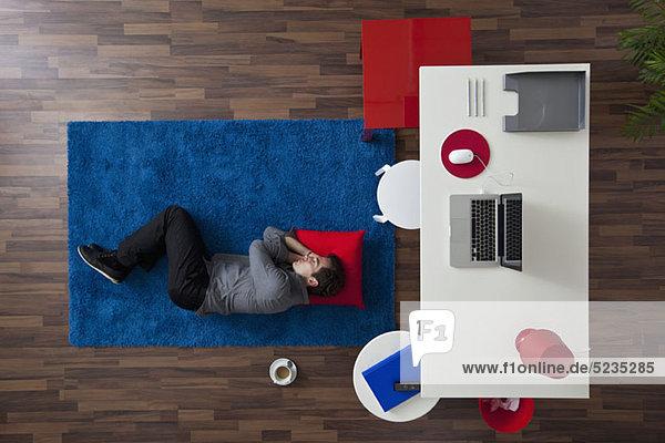 Ein Geschäftsmann  der auf einem Teppich in der Nähe seines Schreibtisches schläft.