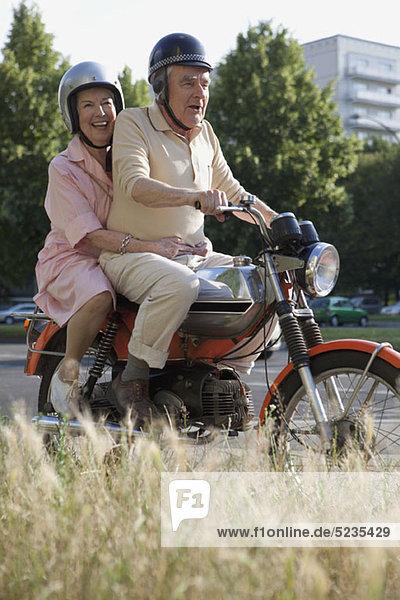 Seniorenpaar glücklich auf dem Motorrad