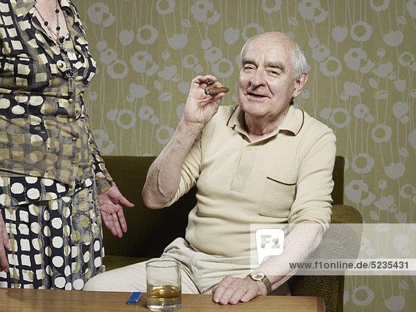 Senior Mann sitzt auf der Couch und raucht Zigarre. Senior Mann sitzt auf der Couch und raucht Zigarre.