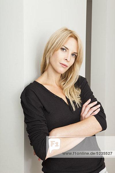 Porträt einer lässigen Frau mit blonden Haaren beim Blick auf die Kamera