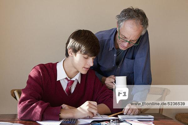 Vater hilft dem Sohn bei den Hausaufgaben