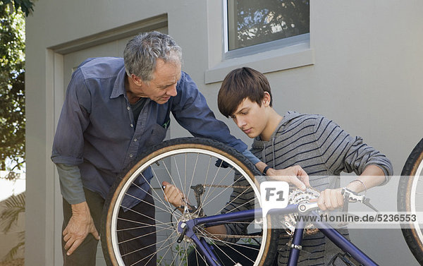 Father helping son repair bicycle