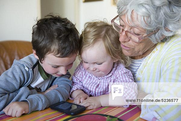 Großmutter und junge Enkelkinder schauen gemeinsam aufs Handy