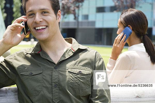 Mann spricht auf dem Handy im Freien mit fröhlichem Gesichtsausdruck