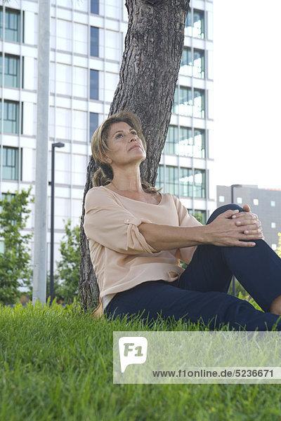 Frau im Gras sitzend  in Gedanken aufschauend