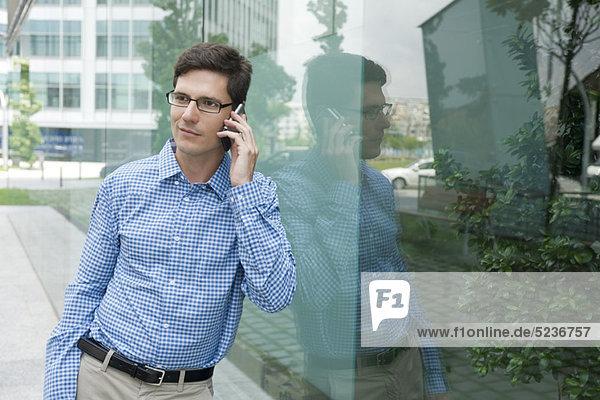 Mann im Button-Down-Shirt lehnt sich an die Glaswand  spricht auf dem Handy