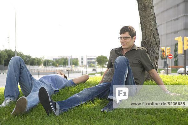 Männer entspannen sich im Gras in der Stadt