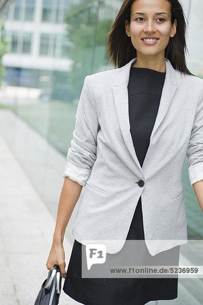 Frau läuft mit Aktentasche
