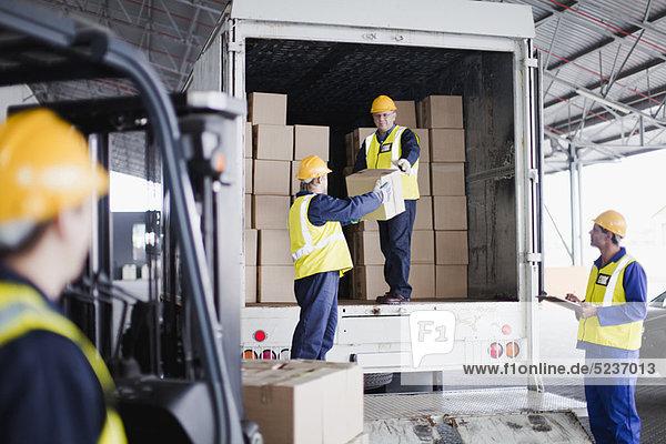 Arbeiter beim Entladen von Kisten vom LKW