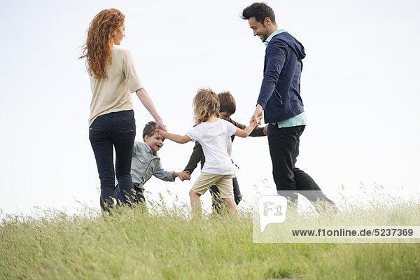 Familie spielen Ring-um-die-Rosy auf Wiese