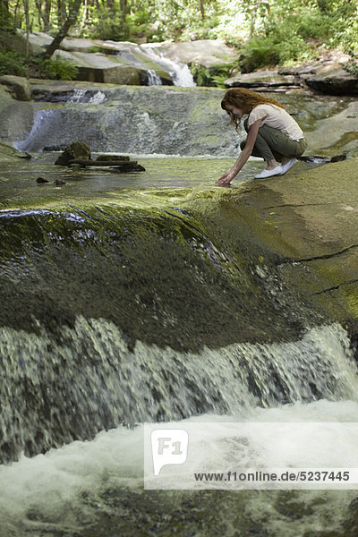 Frau neben kaskadierende Stream  hocken Hände in Wasser eintauchen