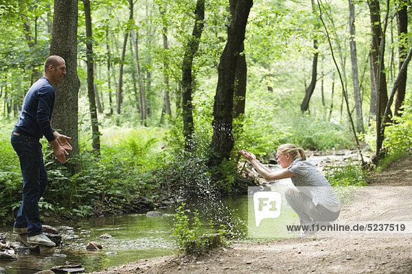 Paar in Wäldern  Frau Spritzwasser Mann