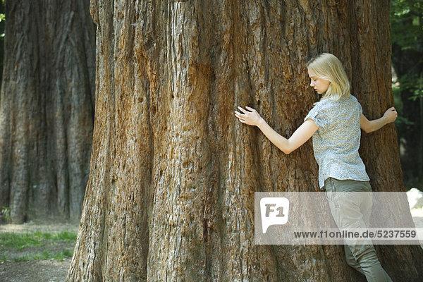 Young Woman hugging Baum mit Augen geschlossen