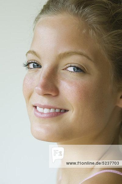Junge Frau  Blick über die Schulter in die Kamera  Porträt