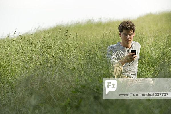 Young Man sitting in Gras-Textnachrichten