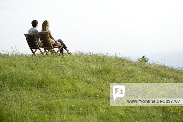 Paar sitzen auf Stühlen über Hügel  Aussicht betrachten