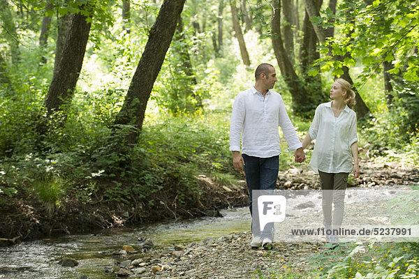 Couple walking von Stream ausgeführt durch Wald