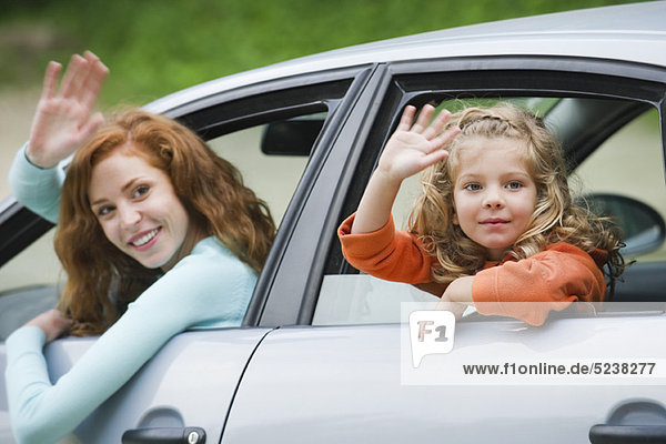 Mutter und Tochter von Autoscheiben  schiefen winken
