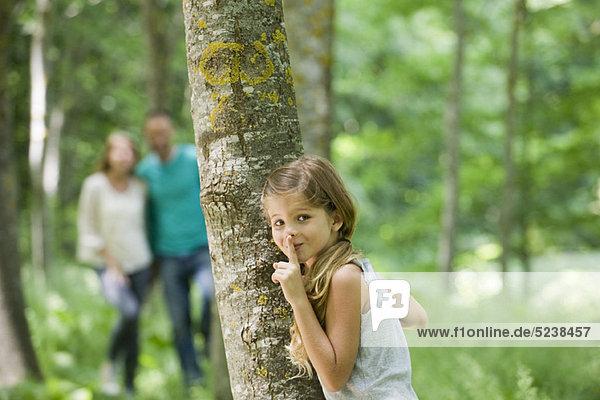 Versteckt sich hinter einem Baum mit Finger auf Lippen Mädchen