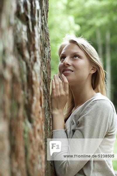 Frau an Baum gelehnt Nachschlagen