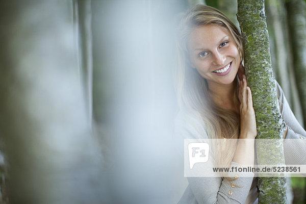 Young Woman leaning gegen Stamm  Fokus auf den Hintergrund