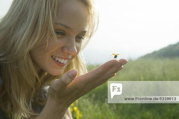 Young Woman holding Marienkäfer als es startet im Flug
