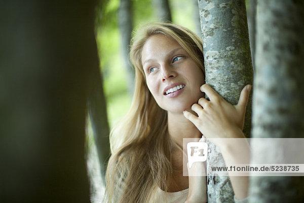 junge Frau knuddeln Baum