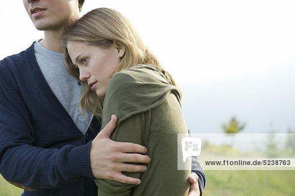 Young woman resting head on boyfriend's shoulder