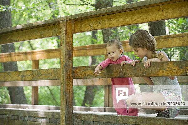Mädchen und ältere Schwester über Geländer der Brücke