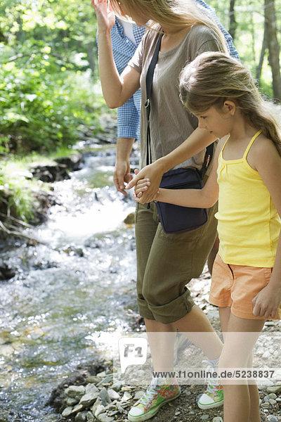 Mutter und Tochter  die zu Fuß und Hand neben stream