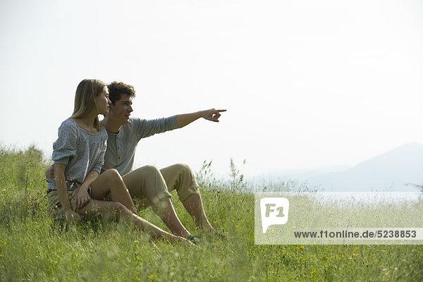 Couple sitting on Wiese  Mann auf Distanz