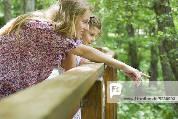Mutter und Tochter über Geländer zusammen