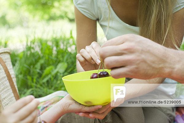 Familie teilen Bowl of Cherries  Außenaufnahme  zugeschnitten