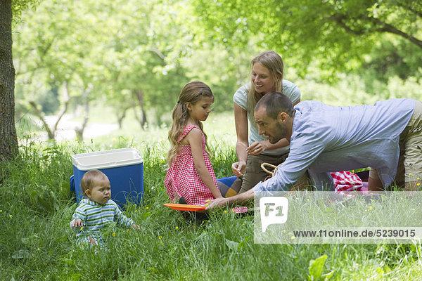 Familie mit Picknick in Wiese