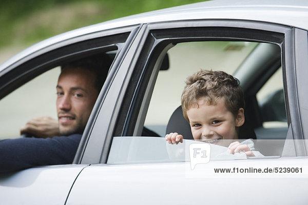 Vater und Sohn Lächeln aus dem Autofenster in die Kamera