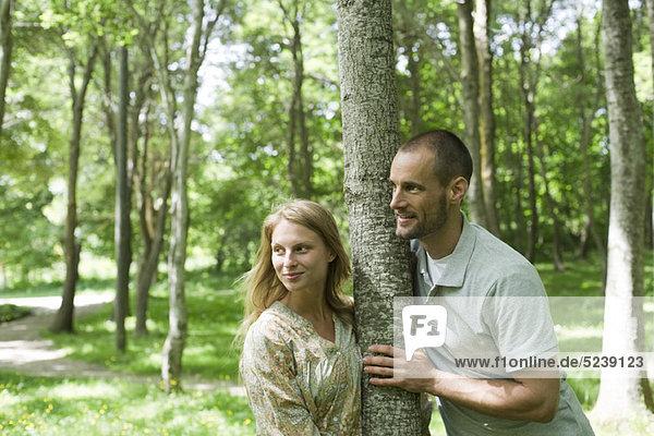Paar an Baumstamm gelehnt