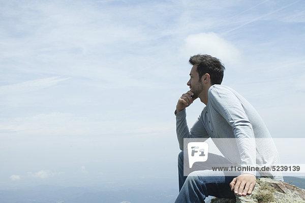 Mann  sitzend auf einem Felsen  Aussicht