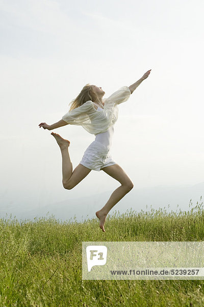 Young Woman jumping in der Luft  Seitenansicht