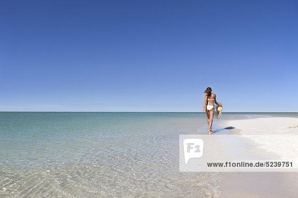 Frau  die Strohhut am Strand