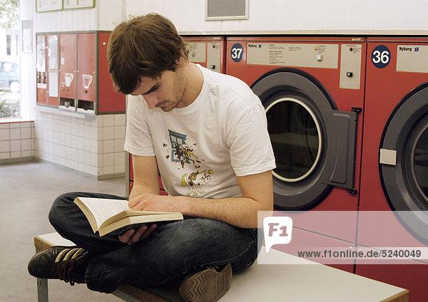 Mann sitzt im Waschsalon  liest ein Buch