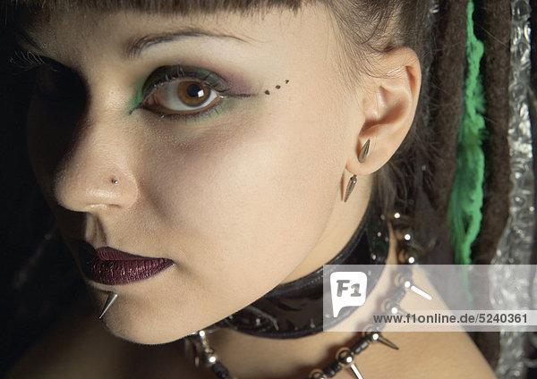 Frau mit Dornen-Piercings an Unterlippe und Ohr  Porträt Frau mit Dornen-Piercings an Unterlippe und Ohr, Porträt