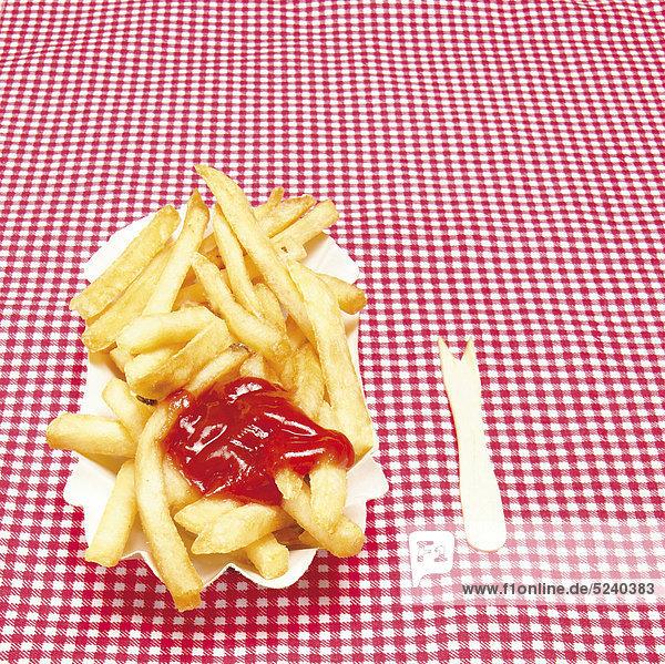 Pommes in Pappschale auf rot-weißer Tischdecke