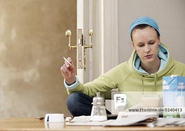 Frau sitzt zuhause am Tisch  raucht und liest