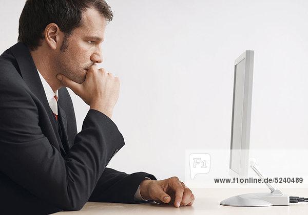 Manager sitzt nachdenklich vor Flachbildschirm
