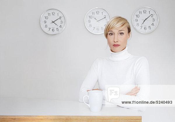 Frau steht in weißem Rolli mit Tasse Kaffee im Büro  Weltzeituhren