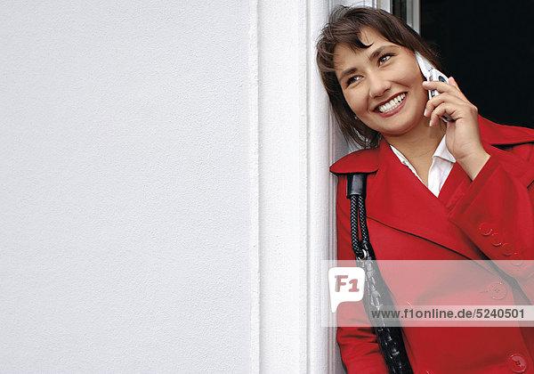 Frau steht an Eingang  telefoniert mit Handy