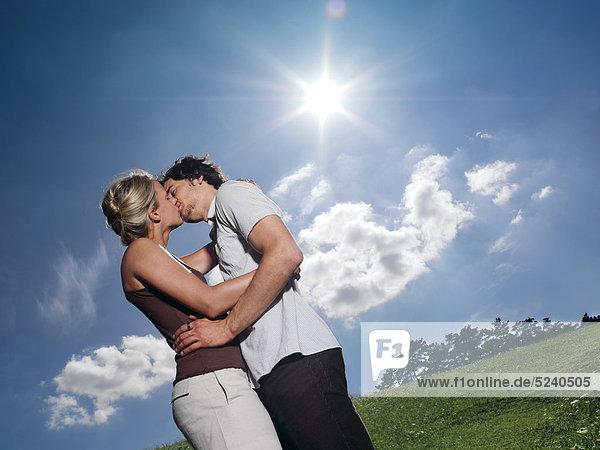 Paar  küssen sich auf Wiese  Sonne